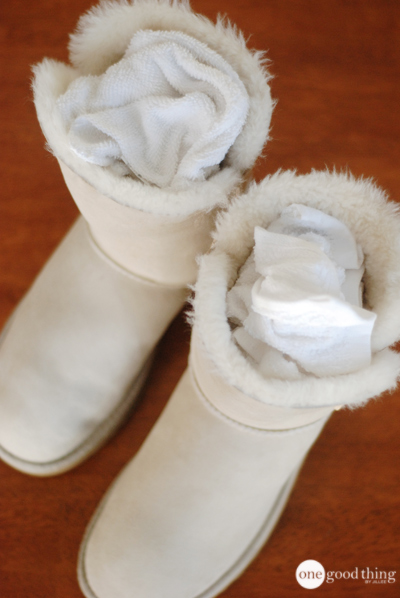 A pair of white Ugg boots stuffed with dry cleaning cloths to help them retain their shape