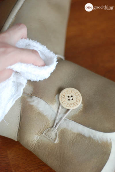 A hand cleaning a white Ugg boot using a wet white cleaning cloth