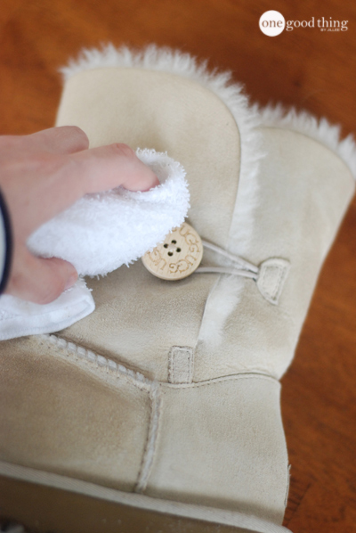 A hand, cleaning a white Ugg boot using a white cleaning rag