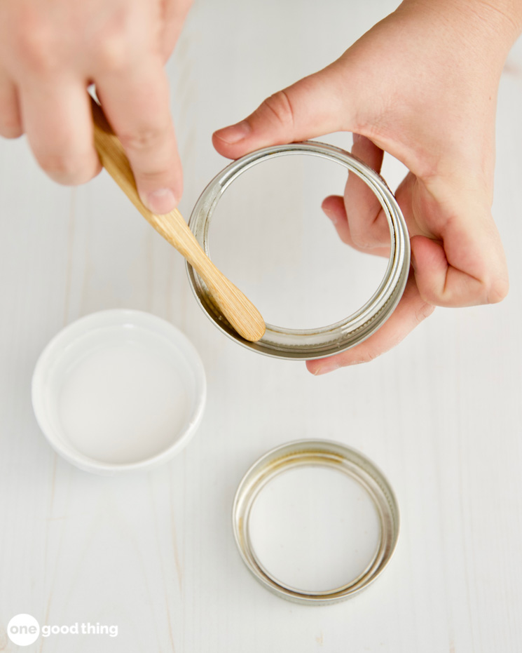 A cream of tartar mixture being brushed onto a metal jar ring to remove rust