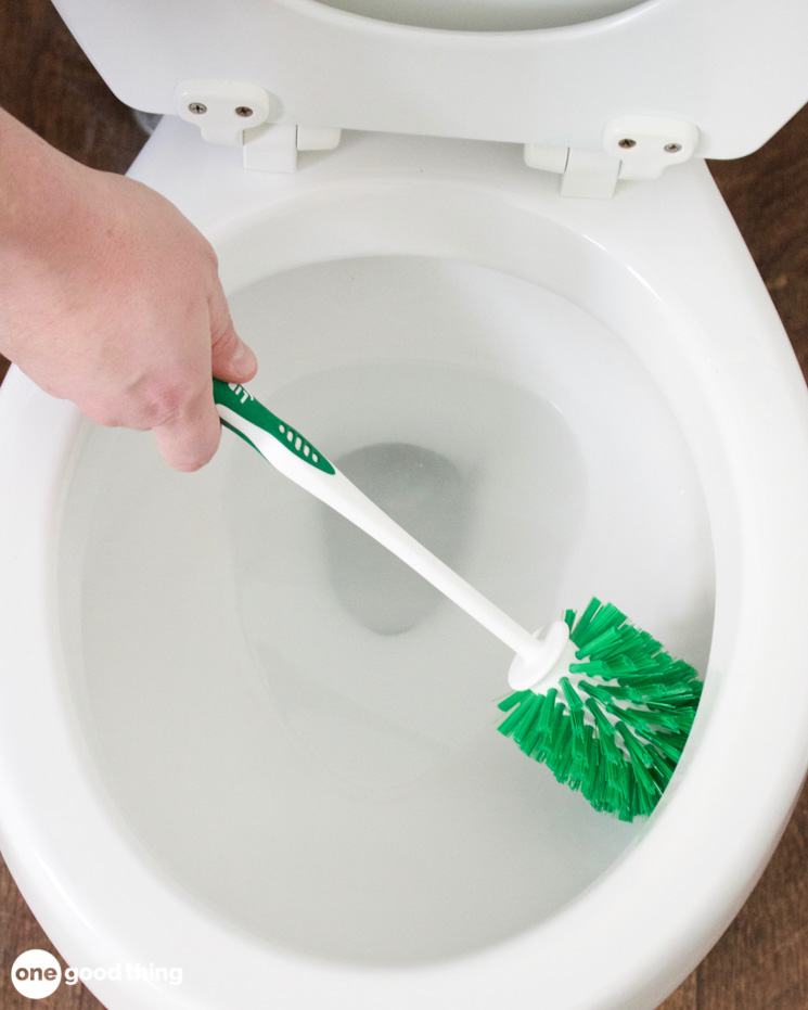 A green and white toilet bowl brush cleaning the inside ring of a toilet